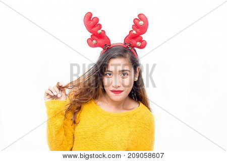 Smiling pretty student in reindeer antler headband touching curly hair and looking at camera. Positive beautiful young woman preparing for Christmas party. New Year concept