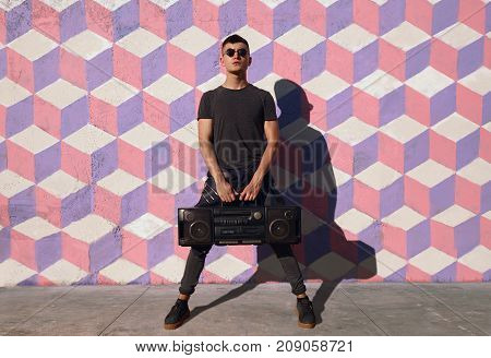 Young hipster man in casual clothing and sunglasses posing with boombox looking at camera.