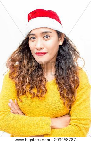 Smiling attractive student girl preparing for Christmas and looking at camera. Portrait of calm confident young woman with curly hair wearing Santa hat and sweater crossing arms. New Year concept
