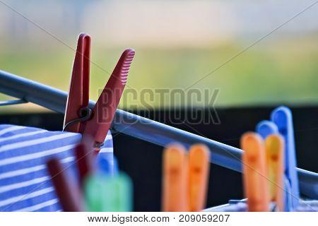 Closeup of several plastic clothespins on a clothes hanger