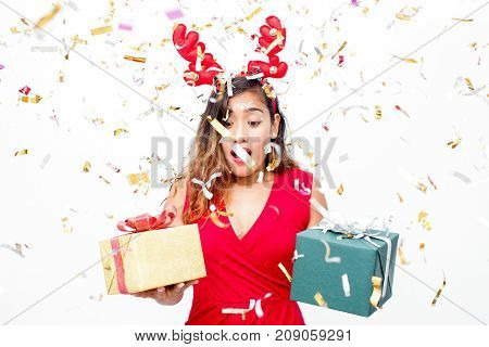 Surprised emotional woman in reindeer antler headband choosing gift under confetti rain. Uncertain expressing young lady in red holding two gift boxes. Fuss before Christmas concept