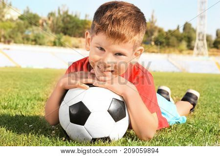 Cute boy with soccer ball on field