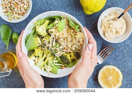 Healthy vegan salad with broccoli and quinoa. Healthy vegan food concept top view dark concrete background.