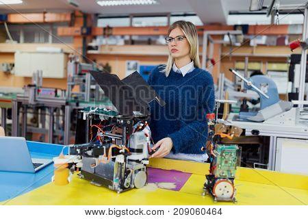 Young beautiful female engineer testing robot at robotics development