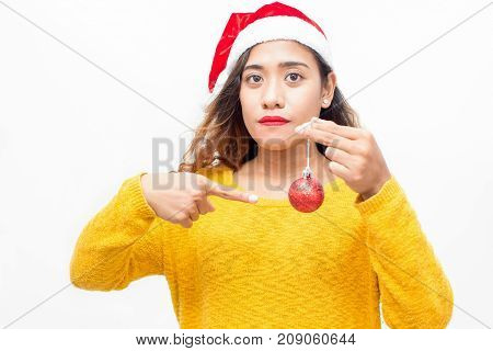 Unsmiling young woman pointing at Christmas ball and looking at camera. Serious attractive girl making hint to start decorating tree. New Years preparations concept