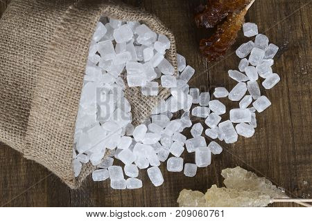 Spilled sugar candy sugar on a wooden surface. White and caramel sugar on a stick.