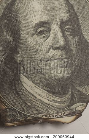 Burning portrait Benjamin Franklin on white background