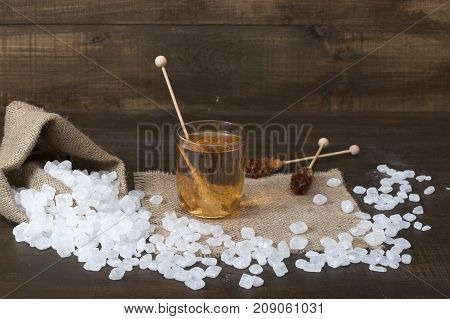 Candy sugar scattered on a brown wooden surface. Sugar on a stick in a glass of green tea