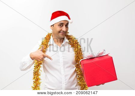 Closeup portrait of content middle-aged handsome man wearing Santa Claus hat, tinsel around neck, looking at camera, holding big gift box and pointing at it. Isolated front view on white background.