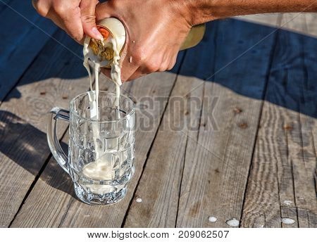 glass mug with beer on the table in the park on sunny summer day