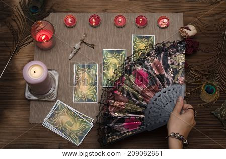 Tarot cards on wooden table of fortune teller. Top view.