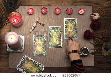 Fortune teller reading future with tarot cards. Paranormal desk table. Fortune teller pointing by finger at Tarot card.