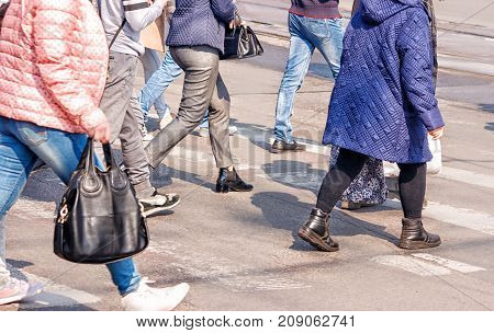 crossroad with walking pedestrians on sunny spring day