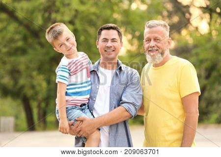 Cute boy with daddy and grandfather in park