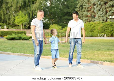 Little boy with daddy and grandfather walking in park