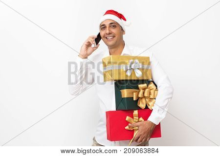 Closeup portrait of smiling middle-aged handsome man wearing Santa Claus hat, looking at camera, calling on mobile phone and holding three gift boxes. Isolated view on white background.