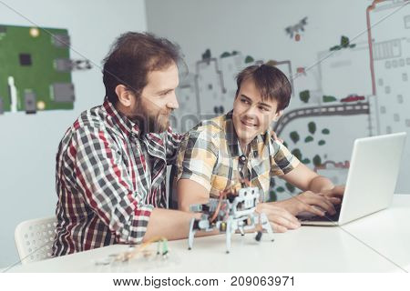 A man and a teenager are sitting at a table in front of a laptop. Nearby is a robot. They program it. Nearby on the table are various parts of robots and tools