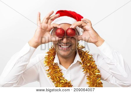 Closeup portrait of smiling middle-aged handsome man wearing Santa Claus hat, tinsel and holding two Christmas balls in front of his eyes. Isolated front view on white background.