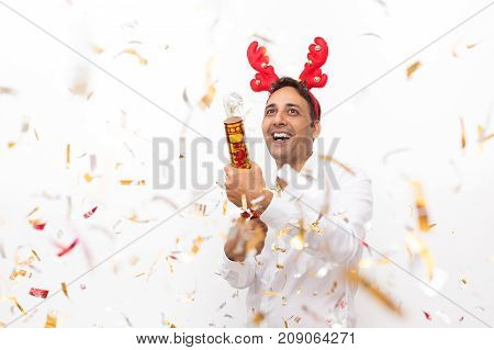 Closeup portrait of cheerful middle-aged handsome man wearing toy reindeer horns and letting off party popper. Isolated front view on white background.