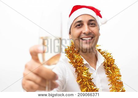 Closeup portrait of smiling middle-aged handsome man wearing Santa Claus hat, tinsel, looking at camera and raising glass with champagne. Isolated front view on white background.