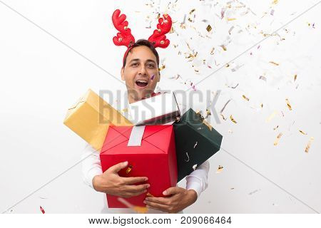 Closeup portrait of joyful middle-aged handsome man wearing toy reindeer horns, looking at camera and holding four gift boxes. Isolated front view on white background.