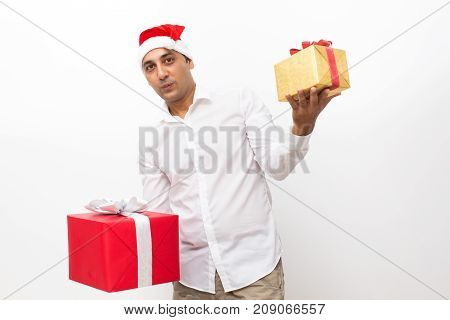 Closeup portrait of pensive middle-aged handsome man wearing Santa Claus hat, holding big and small gift boxes and choosing between them. Isolated front view on white background.