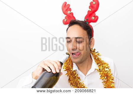 Closeup portrait of smiling middle-aged handsome man wearing toy reindeer horns, tinsel, licking lips and drinking champagne from bottle. Isolated front view on white background.