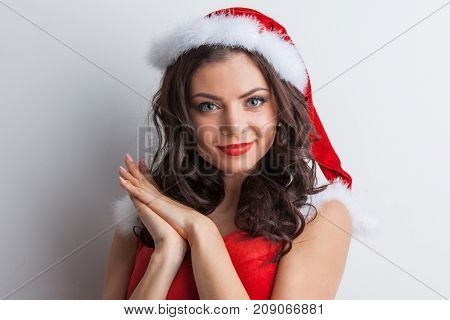 Pretty Pin-up style Santa girl in red hat on gray background