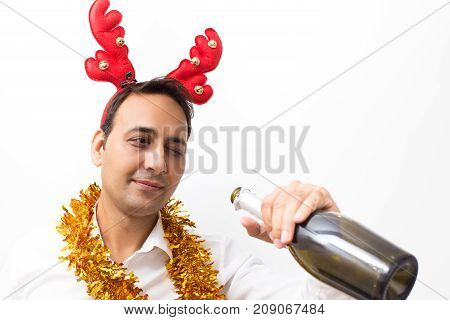 Closeup portrait of content middle-aged handsome man wearing toy reindeer horns, tinsel and looking into champagne bottle. Isolated front view on white background.