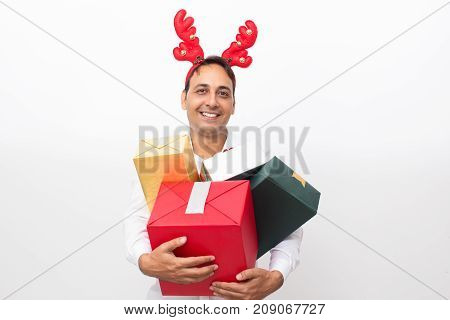 Closeup portrait of smiling middle-aged handsome man wearing toy reindeer horns, looking at camera and holding four gift boxes. Isolated front view on white background.