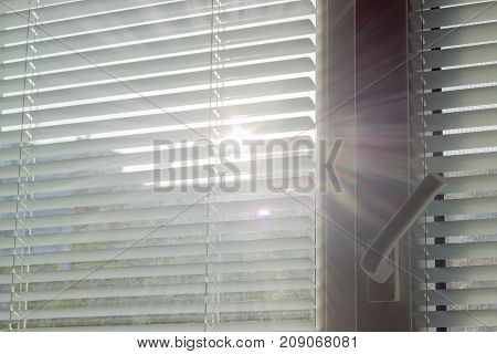 Venetian blinds on the window and sunbeams making their way through the slats of blinds