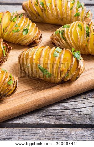 Freshly baked hasselback potatoes with parsley .