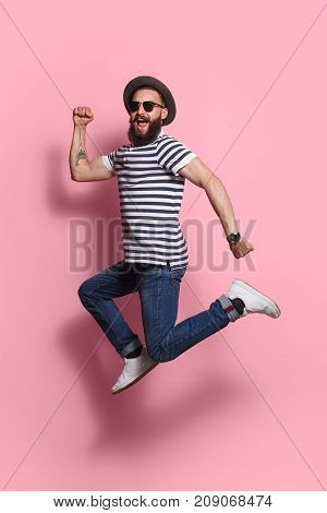 Young excited hipster man in gat and sunglasses jumping and posing on pink studio background.