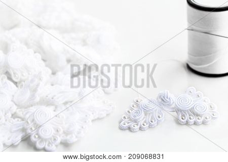 Button knot chinese : A lot of traditional chinese white knot buttons with thread and sewing needle on the white background.