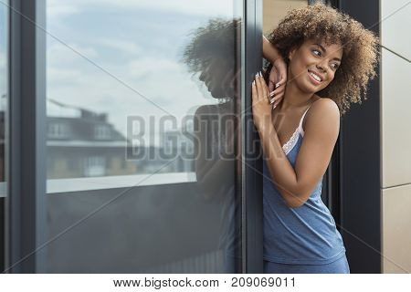 Portrait of cheerful african female leaning on glass door. She wearing pajamas. Copy space