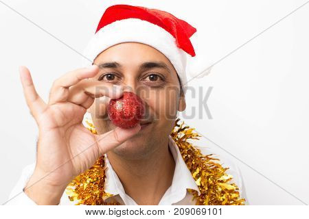 Closeup portrait of playful middle-aged handsome man wearing Santa Claus hat, tinsel and holding Christmas ball in front of his nose. Isolated front view on white background.