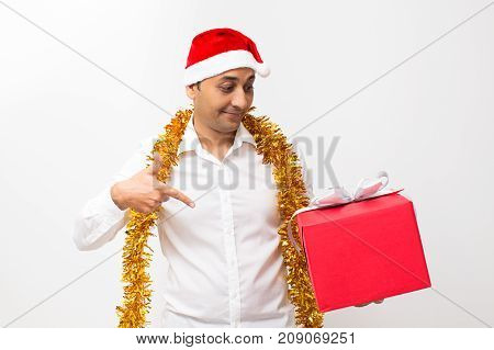 Closeup portrait of content middle-aged handsome man wearing Santa Claus hat and tinsel around neck, holding big gift box and pointing at it. Isolated front view on white background.