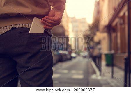 Modern guy holding cellphone in his pocket.