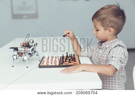 A little boy is playing chess with a gray robot. The robot plays for the whites. The boy makes the first move, the robot watches