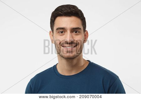 Close Up Portrait Of Smiling Handsome Guy In Blue T-shirt Isolated On Gray Background