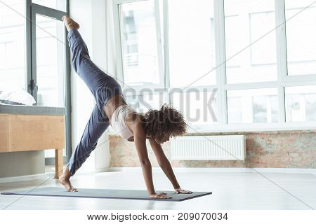 Full length side view serene mulatto woman taking exercise on mat at home. Copy space