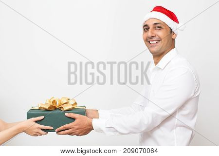 Cheerful handsome man receiving present at Christmas enjoying new years eve at work. Happy Indian male manager holding gift box and looking at camera. Holiday cheer concept