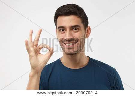 Young Man Having Happy Look, Smiling, Gesturing, Showing Ok Sign. Caucasian Male Showing Ok-gesture