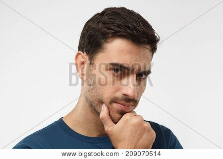 Close Up Portrait Of Young Handsome Male In Blue T-shirt Touching His Chin With Hand Thoughtfully Lo