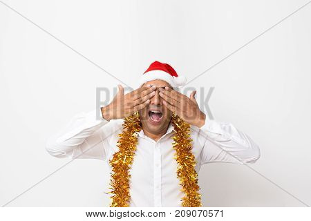 Emotional male manager in Santa hat covering eyes and screaming while receiving shocked news. Thrilled Indian man not believing in his eyes. Christmas sale concept