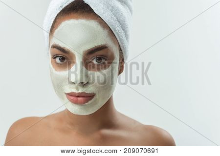 Portrait of serene african girl with mask on face. isolated on grey background. Copy space. Beauty concept