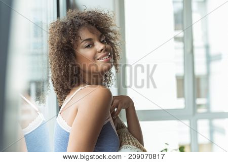 Portrait of mulatto female demonstrating happiness while leaning against window in apartment. Morning concept
