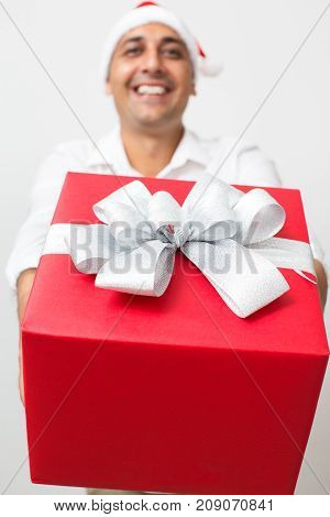 Happy Indian courier delivering Christmas gift wrapped in paper and ribbon. Close-up of big present with white bow. Surprise concept
