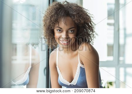 Portrait of outgoing mulatto girl with nice curly hair looking at camera. She locating in apartment