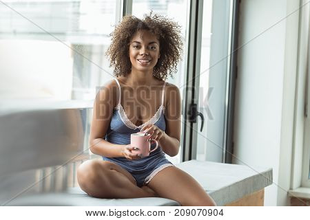 Portrait of cheerful young african lady drinking cup of delicious coffee while sitting on windowsill in room